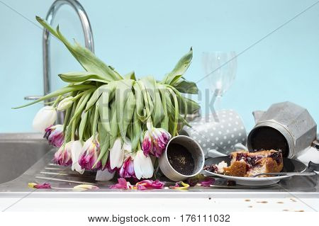 Kitchen in messy condition with food left dirty coffee maker and bouquet of faded tulips