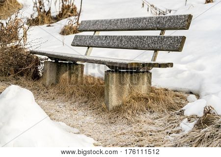 Rustic garden bench outdoors in a snowy park with thick winter snow lying on the ground and frost on the wooden slats of the empty seat