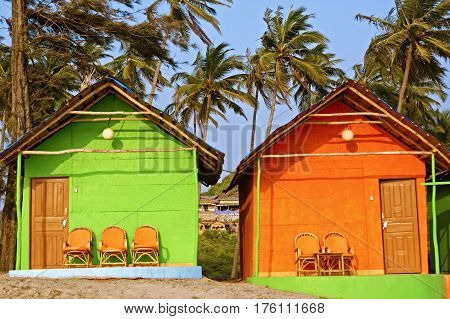 Two Colorful Bungalows on a Palm Beach in Goa, South India.
