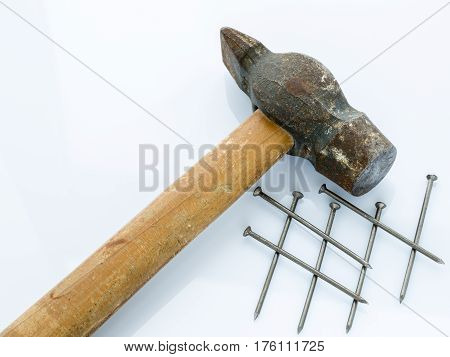 An old hammer with a wooden handle and a bunch of nails. Objects on a light background