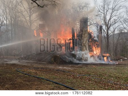 firefighters trying to control fully engulfed house fire