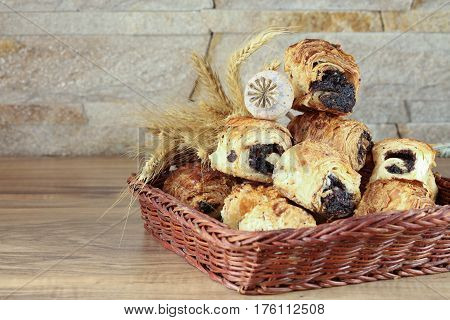 Sweet buns with poppy seeds lie in a wicker basket on a wooden table and near a stone wall - sandstone. Poppy head and spikelets lie on sweet rolls