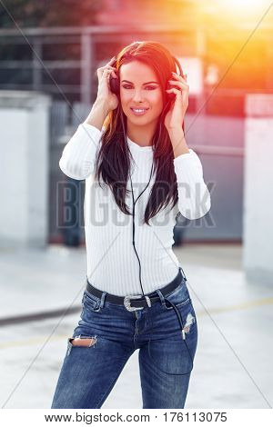 Young woman listening music by headphones in sunset at oudorr