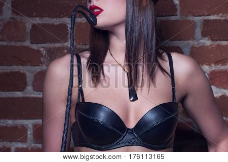 Sexy woman with red lips holding whip closeup bdsm