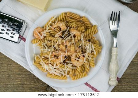 Close-up from above view of homemade pasta with shrimps and cheese in white dish with fork over towel on rustic wooden table