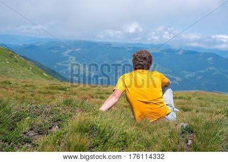 Traveler sitting on an alpine meadow among lush grass and admiring the panorama of the mountains in front of him. Sunny day in the mountains. Back view.