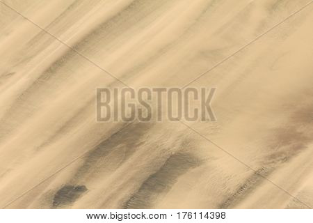 Trails of dust and shifting sand dunes textures. Sand dune texture in african desert. Aerial image photo background.