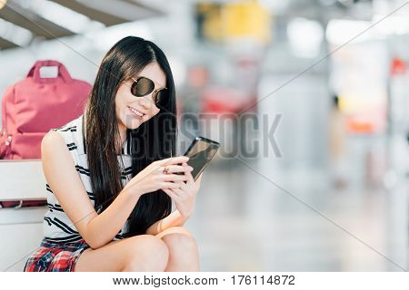 Young Asian girl using smartphone waiting for flight at airport sitting on baggage trolley or luggage cart. Mobile communication technology or travel abroad concept