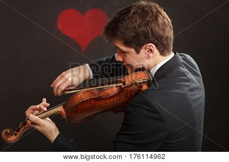 Music passion hobby concept. Romantic young man man dressed elegantly playing on wooden violin. Studio shot on dark background with red heart