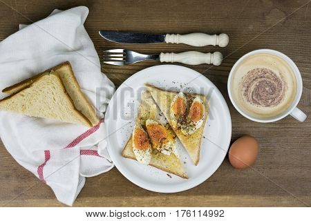 Egg sandwich seasoned with pepper with frothy cappuccino coffee a knife and fork and sliced bread on a rustic wooden table overhead view