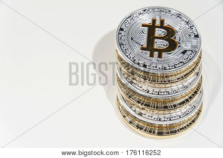 Pile of shining metal BTC bitcoin coins on white background.