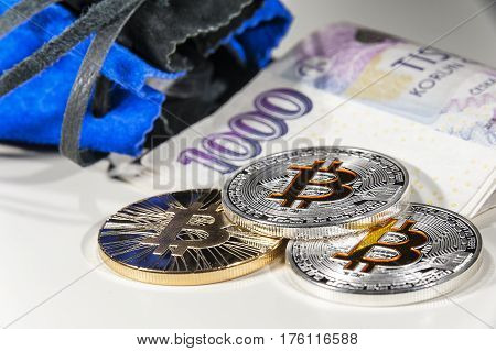 Shining metal gold and silver Bitcoin coins on Czech thousand crowns bank notes with money pouch