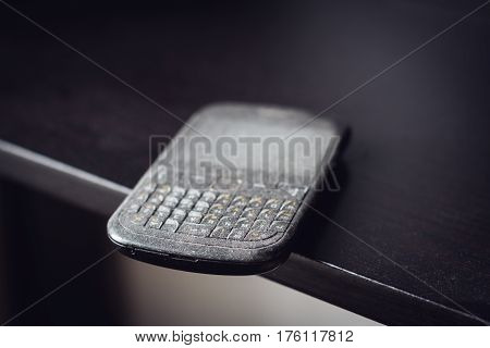 side view close up of old black smartphone mobile with qwerty keyboard covered in dust left on a black wooden shelf