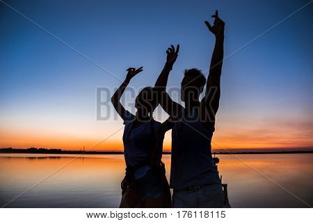 Silhouettes of young beautiful couple resting relaxing rejoicing at sunrise near lake. Copy space.