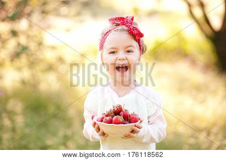 Laughing baby girl 4-5 year old holding white bowl with fresh strawberries over nature green background outdoors. Looking at camera. Healthy eating. Summer time.
