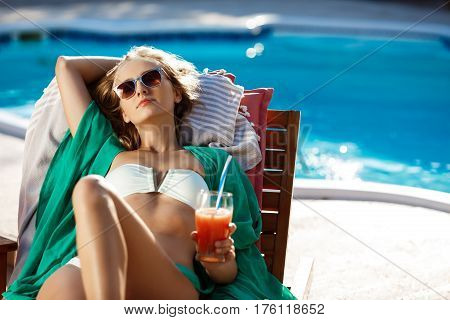 Young beautiful blonde girl sunbathing, drinking cocktail, lying near swimming pool. Copy space.