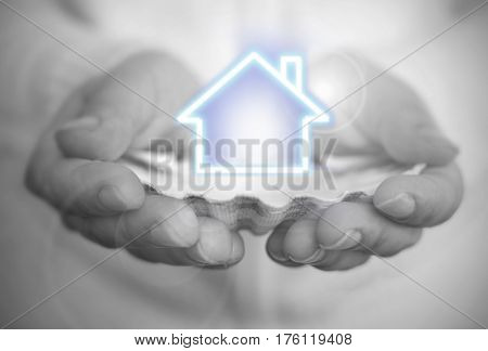 Hand holding a house over an oyster shell