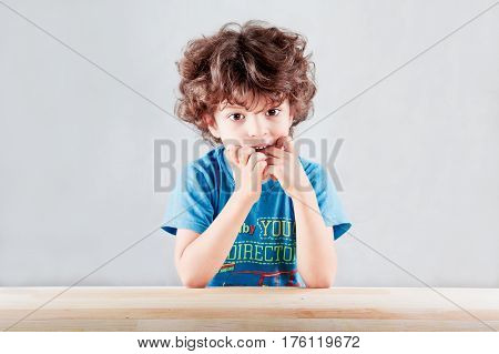The lovely curly-headed kid in a blue t-shirt having thrust fingers listens spellbound in the camera. On a gray background. Close up.