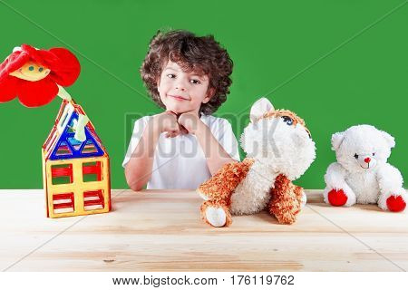 The lovely smiling little boy in a white t-shirt has built the house and shows him to the favourite animals. On a green background.