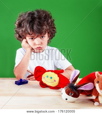 Cute little sad boy close up in white t-shirt offended with his lips with her toys looking at the camera with his head in his hand. On a green background.