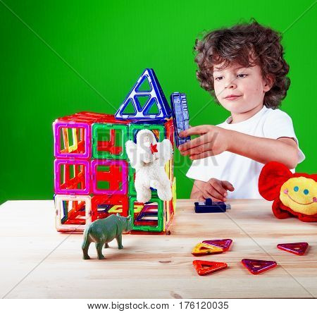 Little cute boy inventor closeup in a white t-shirt builds a tower of magnetic surface. Toys with him building a house. On a green background.