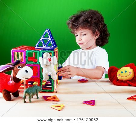 Cute curly boy in a white t-shirt is building a house with friends. Toys help to build a house. On a green background.