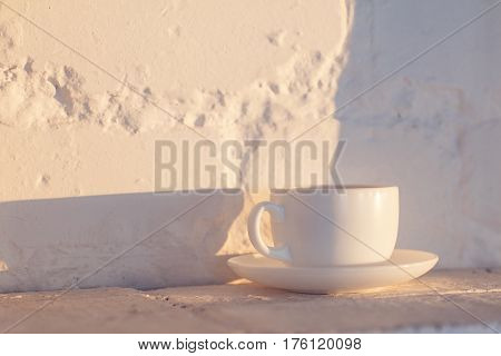 A cup of coffee on a white brick background. Long shadows