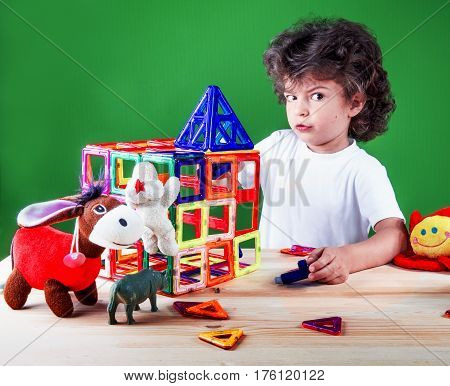 Surprised brown-eyed little boy close up in white t-shirt builds a house with his friends toys. Toys help to build the house. On a green background.