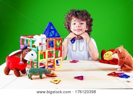 Widely smiling brown-eyed boy close up in white t-shirt looking at the camera. Near built home surrounded by toys.The construction of the house. Toys help to build the house. On a green background.