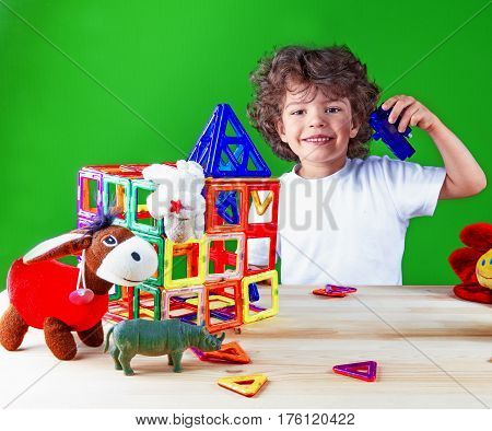 Cute baby in white t-shirt is building a house. Home construction. Toys help to build a house. On a green background.