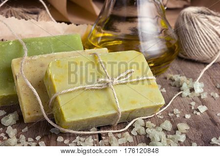 Collection of handmade, natural organic soap and cosmetic oil on wooden background. Spa products. Purple tinted