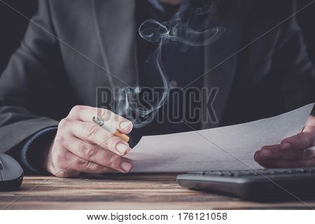 Smoking Businessman Reading Formal Letter. Stressful Atmosphere With Dark Background.