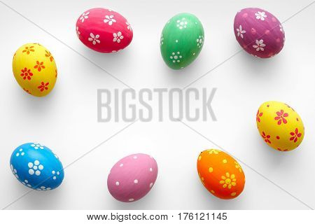 Colorful Easter eggs on white with copy space. Top view. Flat lay.