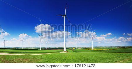Wind turbines on blue sky background. Wind power plants in green meadow. Nice alternative energy background in blue and green colors.