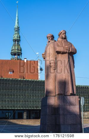 Latvian Riflemen monument Old Town of Riga Latvia. View with spire of St Peter's Church