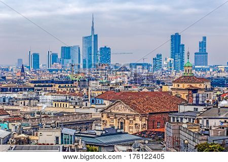 MILAN ITALY - DECEMBER 11 2016: View over Milan from the top of the gothic cathedral Duomo di Milano (Milan Cathedral) Italy. Roof in the foreground skyscrapers of the city in the background.