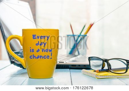 Every day is a new chance. Motivate text on morning coffee cup at business office background.
