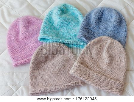 Caps Of Different Colors On A Rag Background, Knitted Wool By Hand On The Spokes