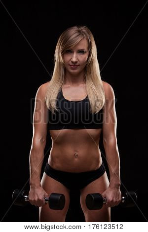 Beautiful athletic woman pumping muscles with dumbbells, isolated on dark background with copyspace.