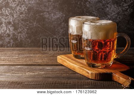 Cold Beer In Glass With Chips On A Dark Background.