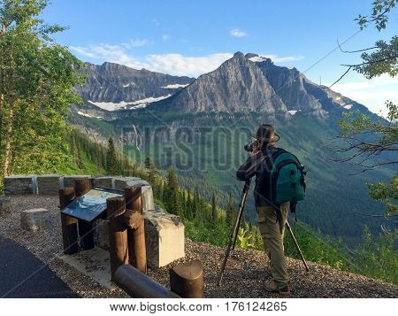 Photographer with backpack taking photos of a majestic mountain in Glacier National park.