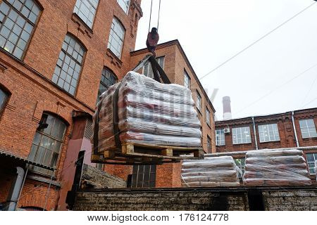 unloading construction bags wrapped in polyethylene on pallets
