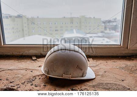 white helmet of the foreman lying on the windowsill