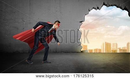 A businessman in a red cape standing in running position on concrete background with a broken hole to the city view. Business and competition. Ready to work. Winners and losers.