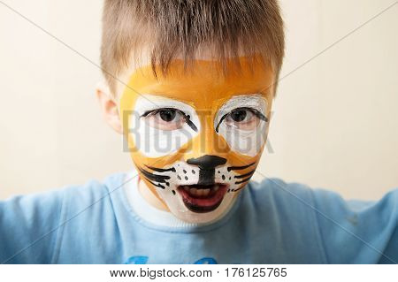Children face painting. Boy painted as tiger or ferocious lion by make up artist. Preparing for theatrical performance. Boy actor playing role. Tiger mask face