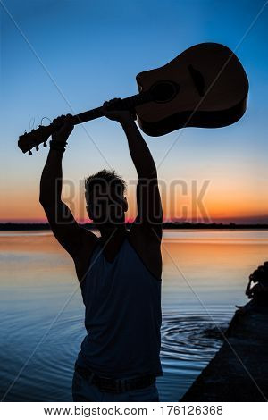 Silhouette of young handsome man holding guitar at seaside at sunrise. Copy space.