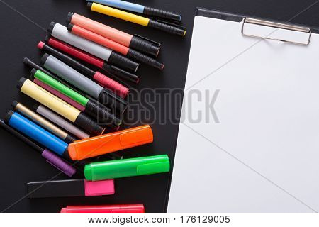 Stationery for drawing - view flat lay shot of many color markers and tablet with blank paper or sketchbook on black desktop background, copy space for text, nobody, objects, close-up