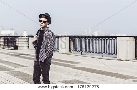 Stylish young man is walking on the city waterfront