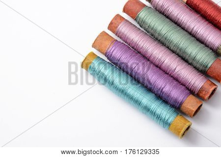 Bright multicolored coils with threads for sewing on white background