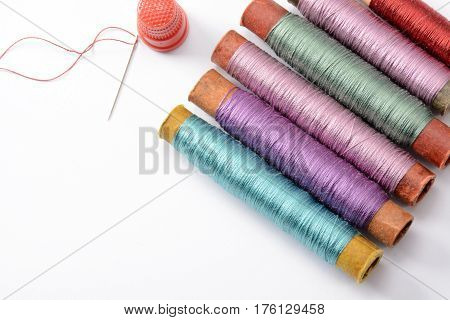Set for sewing, multicolored coils with threads, needle and thimble isolated on white background